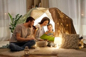 family reading a book in a blanket fort