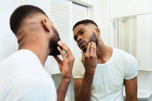 Man looking at beard in the mirror